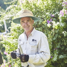 Photograph of a man holding tools in a garden
