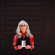 Woman against dark background holding photograph.