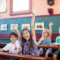 Enthusiastic kids with hands up in old-fashioned school room.