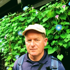 Horticulturist Craig wearing a cap and a blue shirt stands in front of a green climbing plant which has purple flowers