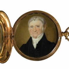 Opened round flip case with miniature painting of man inside.