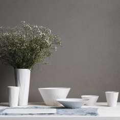 Range of white ceramic objects on table, one a vase holding flowers.