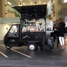 Black retro scooter truck being used as coffee cart.