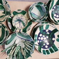 Collection of patterned ceramic plates, bowls and other objects.