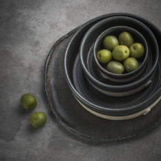 Stacked dark grey ceramic plates and bowls with green fruit in top bowl.