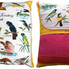 Two cushions with bird designs on fabric.