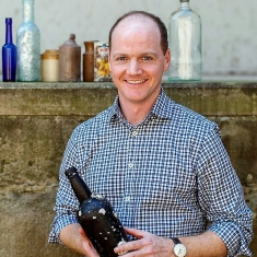 Head and shoulders portrait of man standing holding old bottle and in front of shelf of bottles.