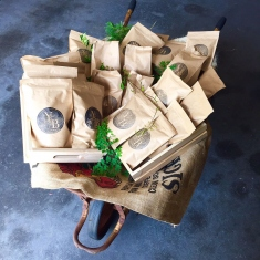Wheelbarrow filled with a hessian bag, wooden trays and paper bags of coffee.