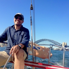 smiling man seated on the back of a boat wearing cap and sunglasses with red ensign flag waving, with blue water and Sydney Harbour Bridge in the background, under blue sky.