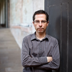 Portrait of man in dark shirt against sandstone wall.