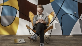 Photo of man sitting in front of a mural