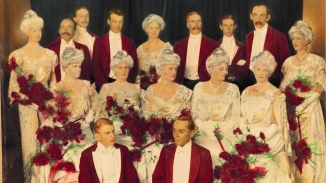 Hand coloured group photo with men in red jackets and women in white dresses holding red flowers.