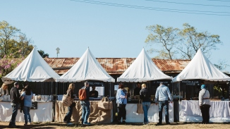 Outdoor market stalls in farm setting.