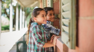 Two children looking in through window of salmon coloured building.