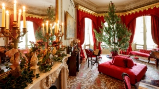 Ornately decorated drawing room with Christmas tree in large window with red drapes.