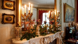 Flowers, decorations and lit candles on ornate mantlepiece with large mirror above.