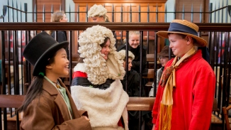 Children dressed up in costumes in courtroom setting.