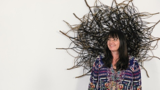 Woman with large circular woven sculpture behind her head.