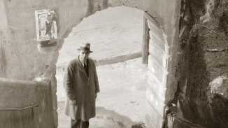 Black and white photo of man in hat and long coat looking up stairs through archway.