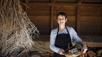 Jacqui Newling holding a basket of ginger and jam melon in wood shed at Vaucluse House.