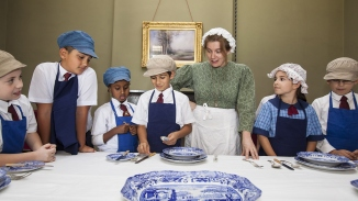 Students & guide standing around the dining table looking at crockery & cutlery
