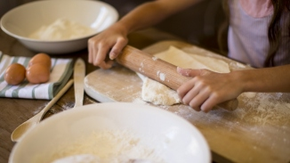 Detail of a girl's hands rolling out pastry dough