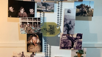 Wall with photos of army personal from the Vietnam war and ID tags