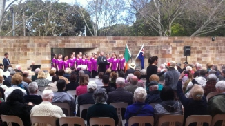 Crowd of seated people in front of group of singers in purple blazers against backdrop of sandstone wall.