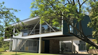 Modernist house in garden setting with tree in right foreground.