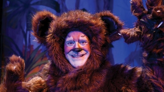 Actor dressed as brown furry animal in stage production.
