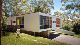 Exterior of Rose Seidler House with woman on lawn.
