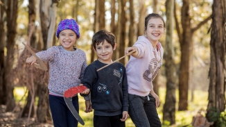 Three children with boomerangs poised to throw them, with trees as background in outdoor setting.