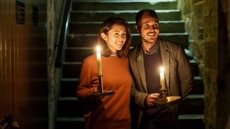 A man and a woman entering the cellar holding candles at Elizabeth Bay House