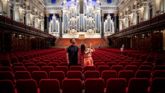 Couple in seating area of large space with ornate organ behind and mezzanine seating above.