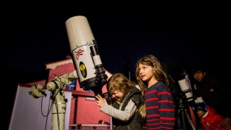 Two girls with telescope at night in front of red building.
