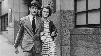 Man in suit and hat with woman in dress and cardigan outside stone facade of building.