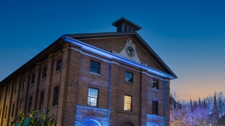 Front of brick building lit up with blue lights against night sky.