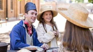 Man dressed in blue coat and convict cap with two girls dressed in shirts and straw hats.