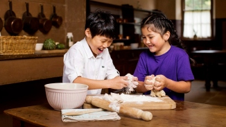 Two kids working with dough at wooden table.