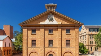 Front of brick three storey building with bellcote and clock visible.