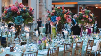 Long table set for banquet in courtyard with guests in background.