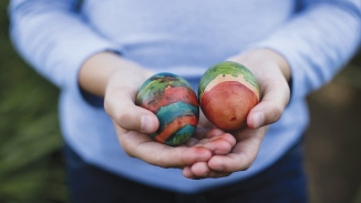 Child's hands holding two painted easter eggs