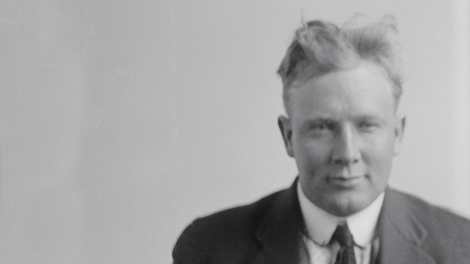"Black and white photo of a blonde man in a suit with scruffy hair. He is smirking. ""8.4.2.J.Cutmore 5.7.22"" is hand written on the image."