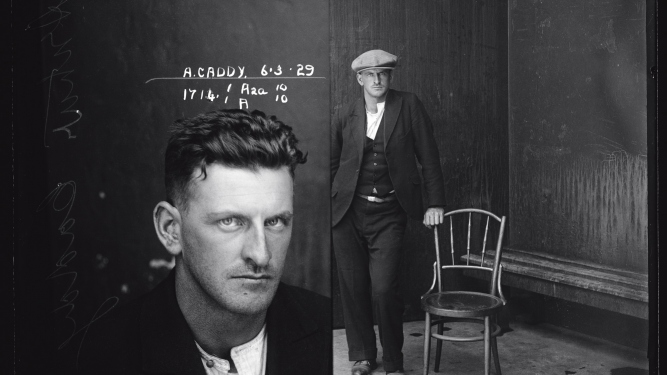 Dual mugshot in black and white; man seated and then man standing, with cap on.