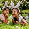 Boy and girl laying on grass wearing bunny ears