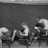 Photo of three boys reading with bad posture while sitting in school chairs.