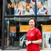 Woman in red shirt outside glass entrance to museum building.