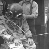 Men surrounding diver in iron diving mask and suit.