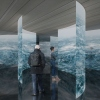 A colour image showing two people looking at what look like projected images on curved screens showing the ocean.