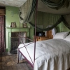 Interior of small green-painted bedroom with four poster metal framed bed and fireplace.